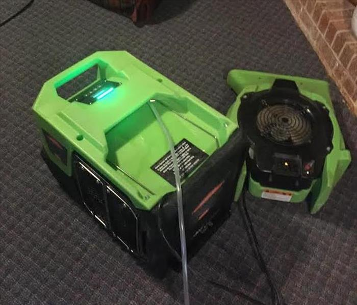 A dehumidifier and air mover drying a basement