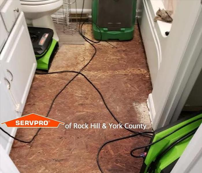 air movers and a dehumidifier drying a wet floor